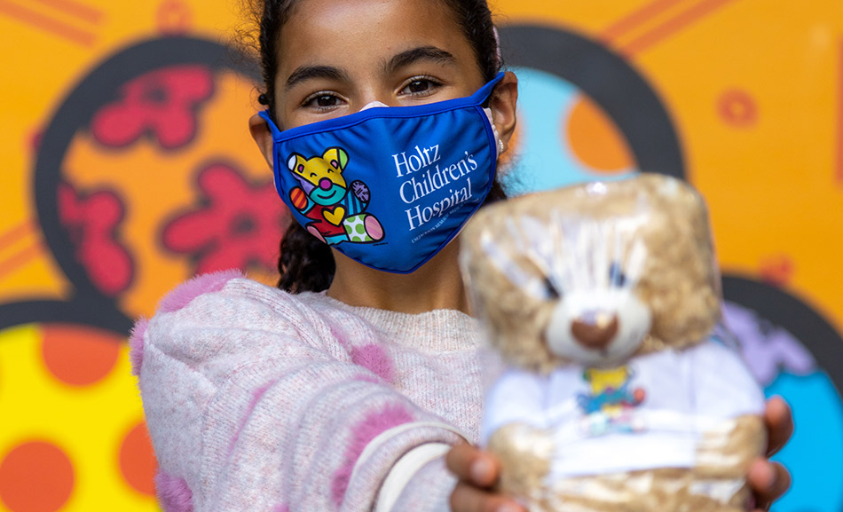 Young girl holding a teddy bear, she wears a face mask that reads Holtz Children's Hospital