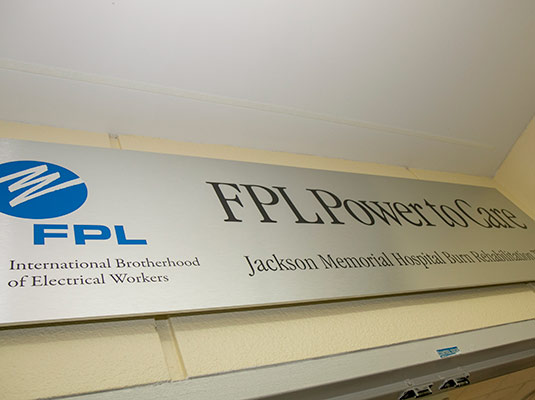 A sign that reads FPL Power to Care Jackson Memorial Hospital Burn Rehabilitation