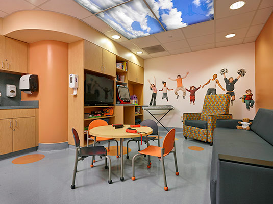 An empty room full of chairs, games; there is an image on the back wall of children jumping and joyful