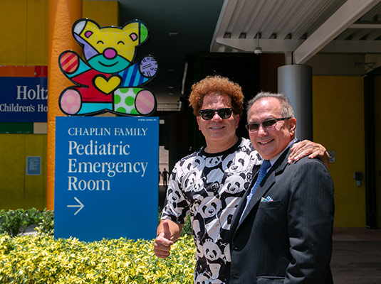 Two men standing outside smiling at the camera, they stand in front of artwork of a bear and a sign that reads Chaplin Family Pediatric Emergency Room