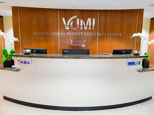 A medical reception area, a sign reads VUMI International Patient Reception Center