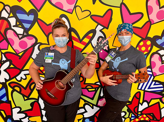 Two medical workers with face masks on playing guitars in front of a colorful wall