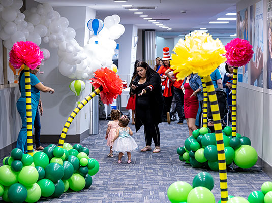 Two children walking in a hospital hallway that has been decorated with balloons, there are medical workers and parents around them