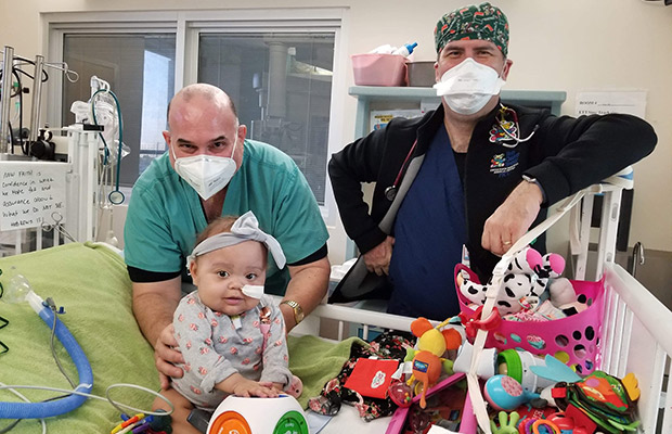 Baby at the hospital with two physicians near her