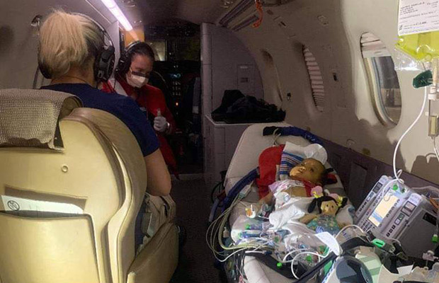 Baby in a flight with medical devices and two medical professionals