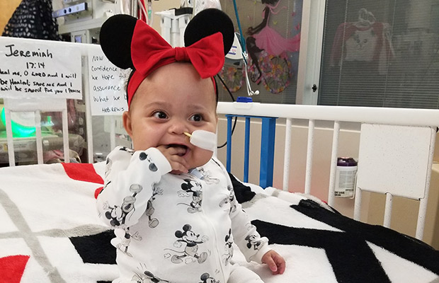 Baby smiling, she is on a hospital bed with a tube coming out of her nose