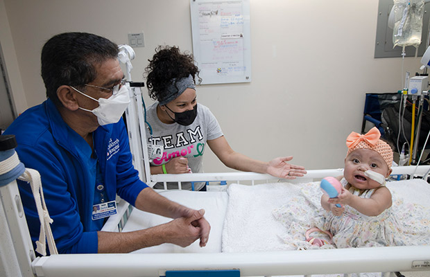 Baby in a hospital bed surrounded by a medical professional and woman