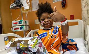 A young child in a hospital bed smiling as he holds a toy box and has one thumb up