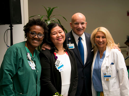 A man standing next to three woman health professionals, they all smile at the camera