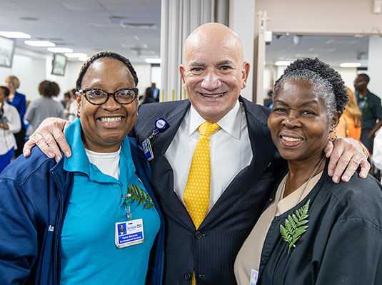 A man and two woman who are health professionals smiling at the camera