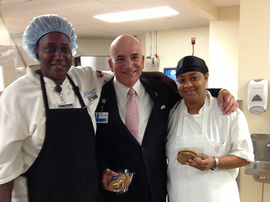 A man and two staff members are smiling at the camera, two of them hold cookies in their hands
