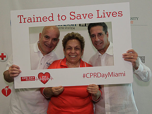 Two men and a woman smiling as they hold a sign around them that reads Trained to Save Lives CPRDayMiami