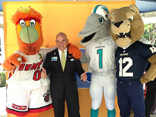 A man smiling as he stands next to three mascots, one mascot is a dolphin, one is a fireball, and a panther