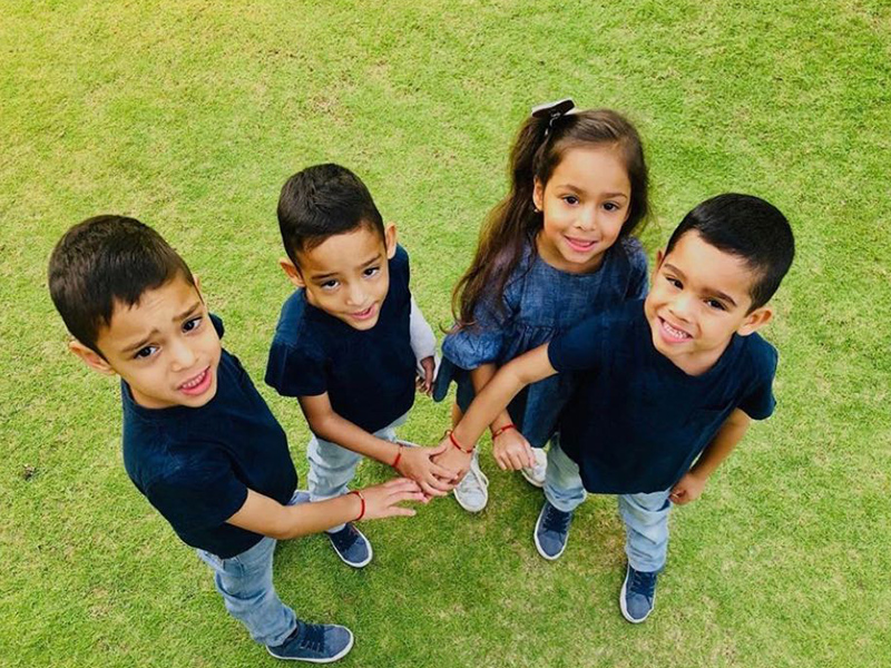 Gutierrez quadruplets standing next to each other, there are three boys and one girl, they are placing their hands in the middle