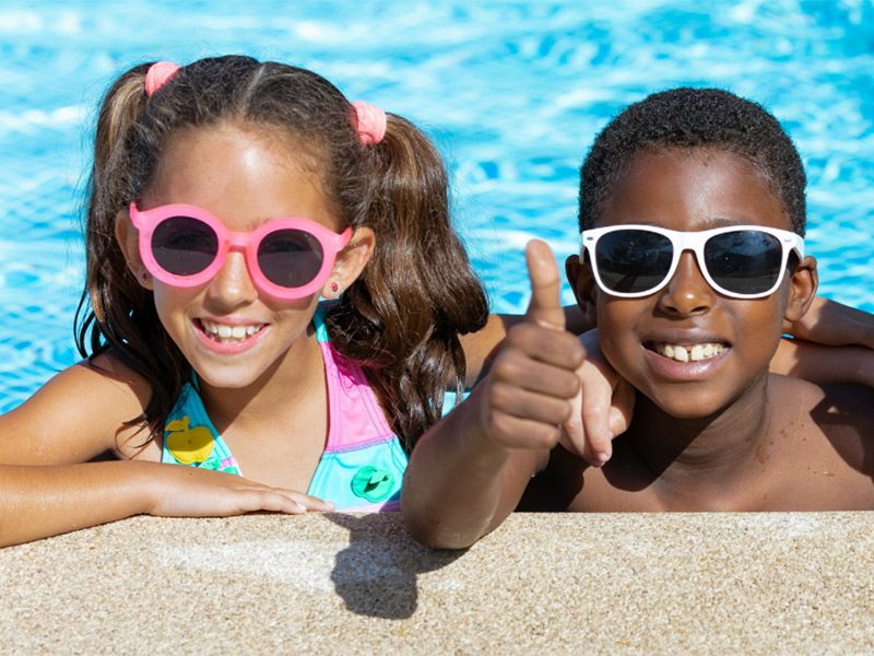 Two young children smiling at the camera, they are in the pool, both are wearing sunglasses and one child is giving a thumbs up
