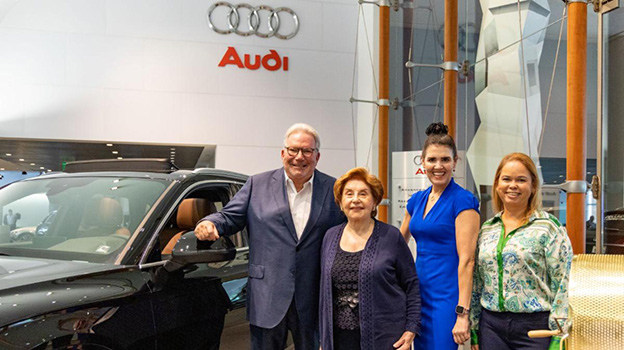 Four adults, one man and three woman, standing next to a black Audi vehicle within a car dealership, they are all smiling at the camera