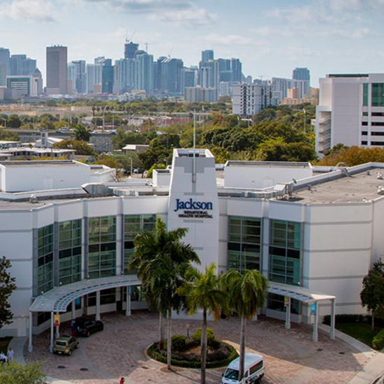External view of a large white building with the city of Miami in the background