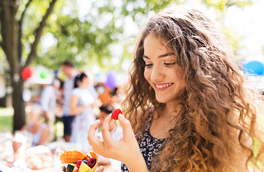A closeup of a woman holding a raspberry