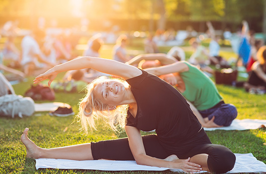 A large group of people doing yoga outdoors