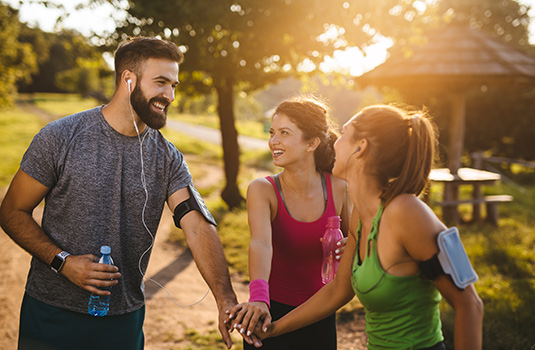 A group of three friends, a man and two women, outdoors wearing workout attire, they have their hands in the center