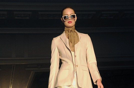 A woman on a runway, she is wearing glasses, a peach colored jacket, and brown scarf