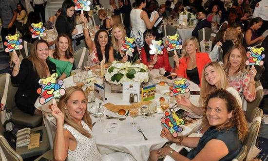 A large group of woman sitting around a circle table and holding bear signs, they all look at the camera
