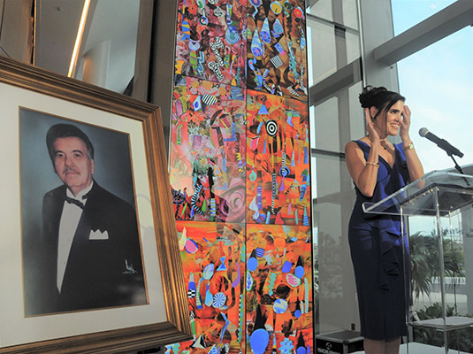 Woman clapping her hands, she's standing in front of a podium standing next to an image of a man in a suit