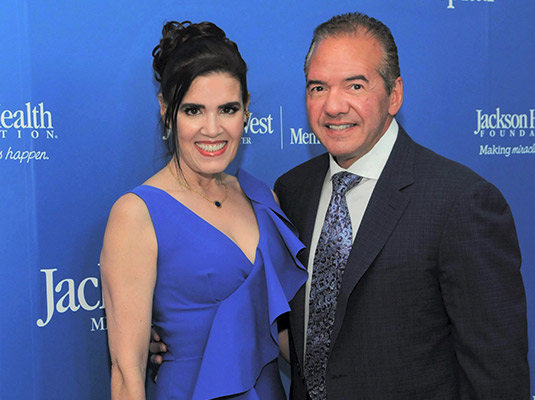 A man and woman smiling at the camera, they are standing in front of a blue step and repeat