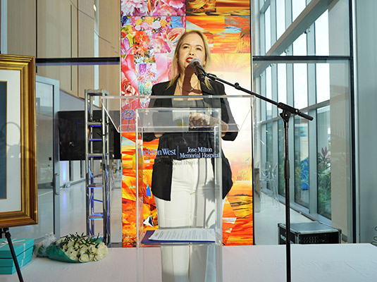 Woman in front of a podium speaking into a microphone