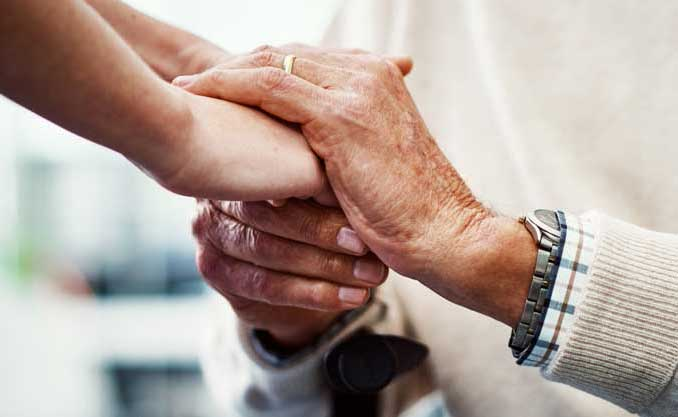 Elderly person holds hands with a younger person