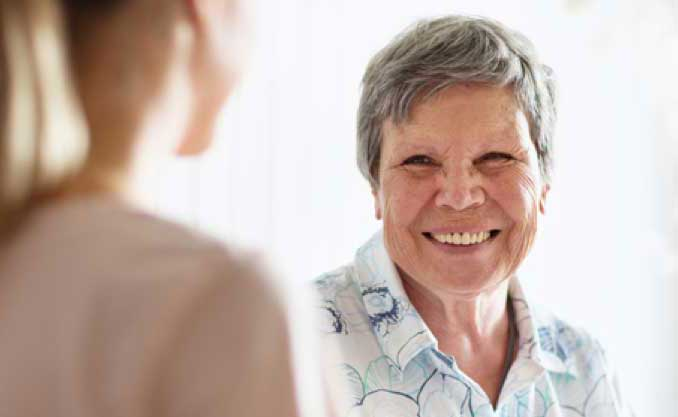 An elderly woman smiles at a woman