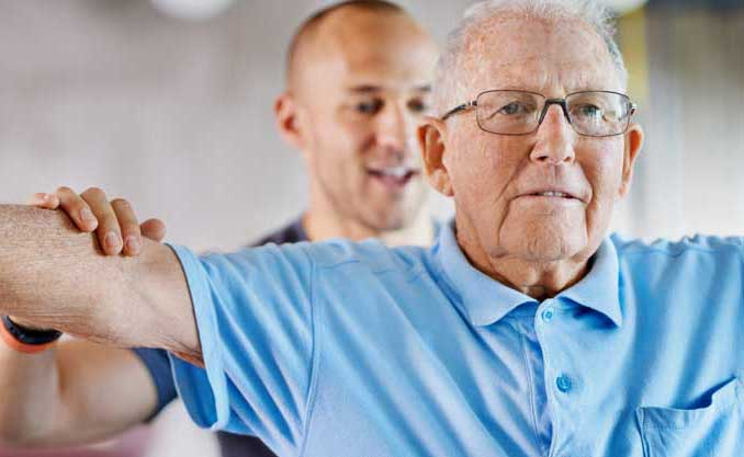 A rehabilitation specialists goes through exercises with a senior man