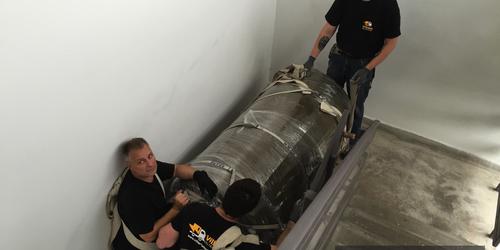 1000 literes melegvíz tároló tartályok (265 kg/db) szállítása 2. emeleti kazánházba.