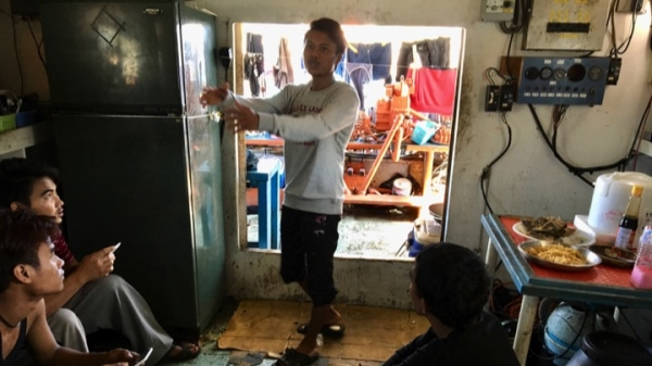 Indonesian fishermen chat in a small, musty living quarters on a fishing boat in Taiwan.