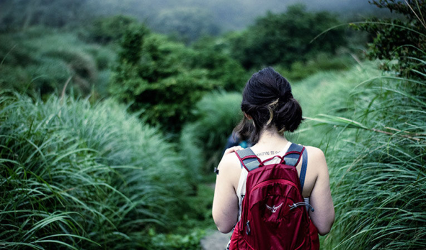 woman with red backpack walking through tall grass in Taipei