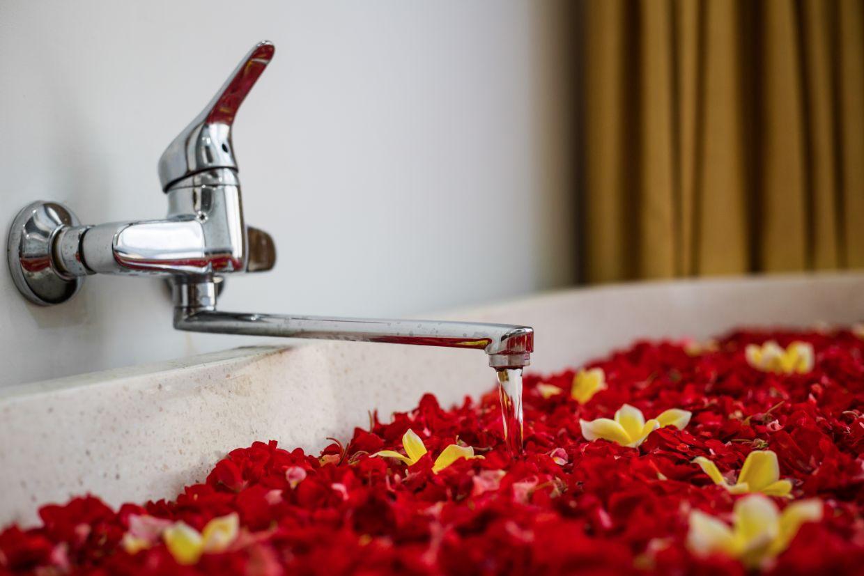 red flower on bathtub of luxury hotel Karma Spa at Karma Mayura