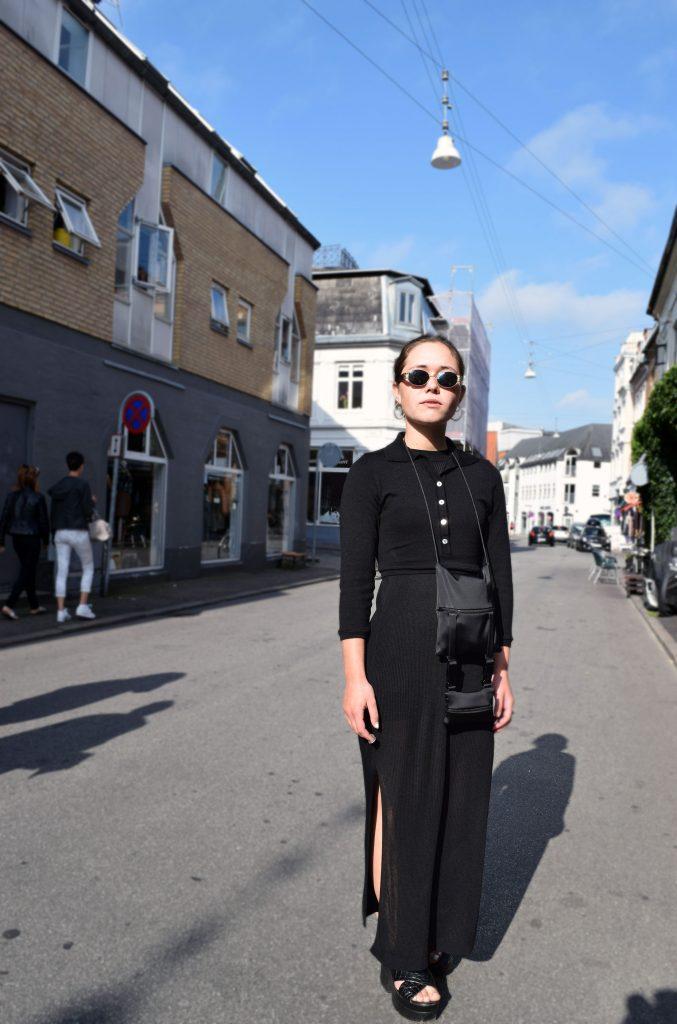 Street style danois à Aarhus, robe noires, pull noire, sandale noires et sac à bandoulière.