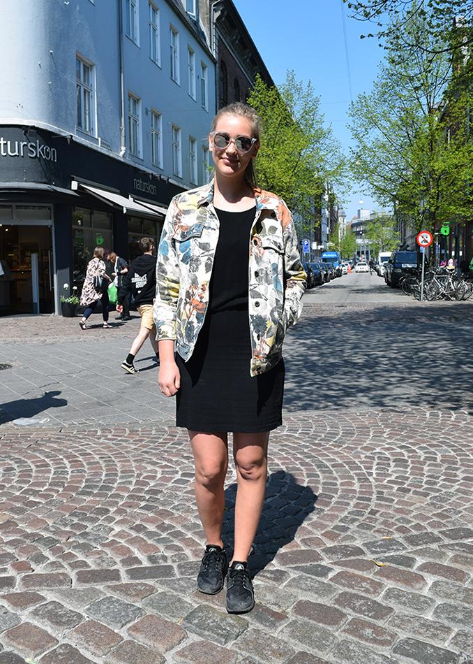 Street style danois, femme avec veste a fleurs, robe noir et basket noires.