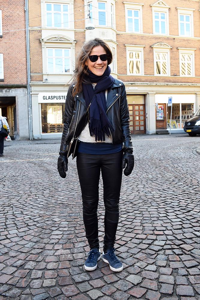 Street style danois à Aarhus, femme avec une veste en cuir, un pantalon en daim et une echarpe bleu foncé.
