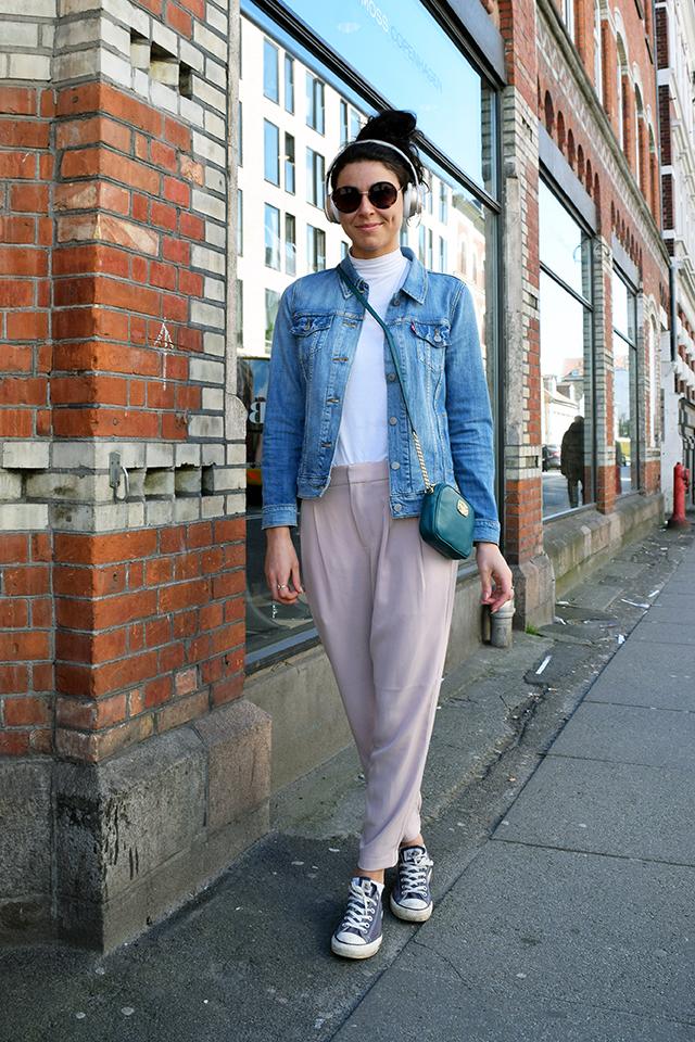 Street style danois à Aarhus, pantalon rose, veste en jean, sac a bandouliere et des baskets gris Converse