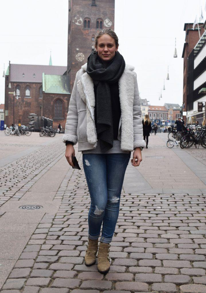 Street style danois à Aarhus, femme avec des bottes beiges, jean devasé et une veste fourrée et une grosse écharpe noire.