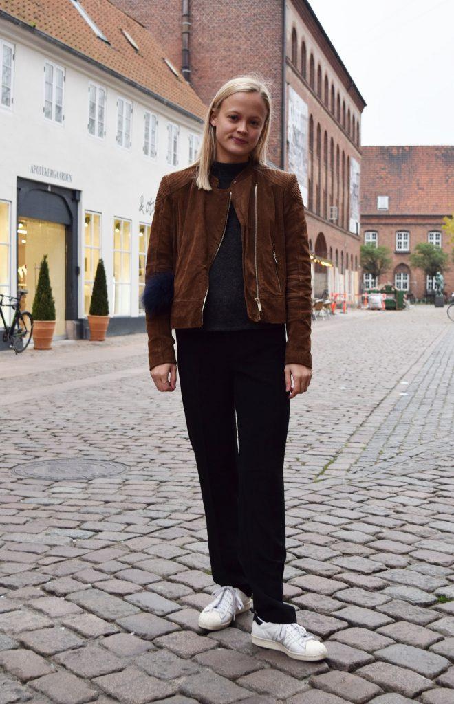 Street style danois à Aarhus, femme avec une veste en cuir, un pantalon de costume noire et des baskets blanches.