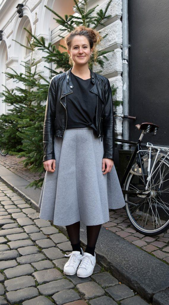 Street style danois à Aarhus, femme avec une jupes grise, baskets blanches et une veste en cuir au dessus d'un t-shirt noir.