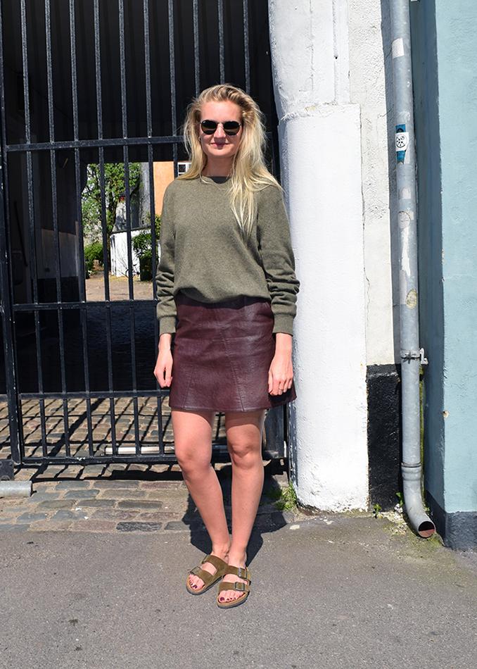 Street style danois à Aarhus, femme avec une jupe en cuir, une blouse cashmere kaki et des sandale en cuir.