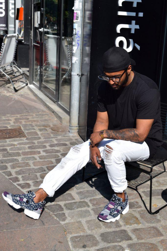 Street style danois à Aarhus, homme a jean blanc avec baskets reebook et une casquette noire.