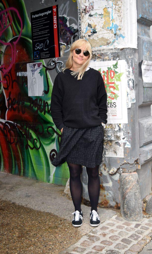 Street style danois à Aarhus, femme avec une jupe noire et un pull noir et des baskets adidas noire et blanches.