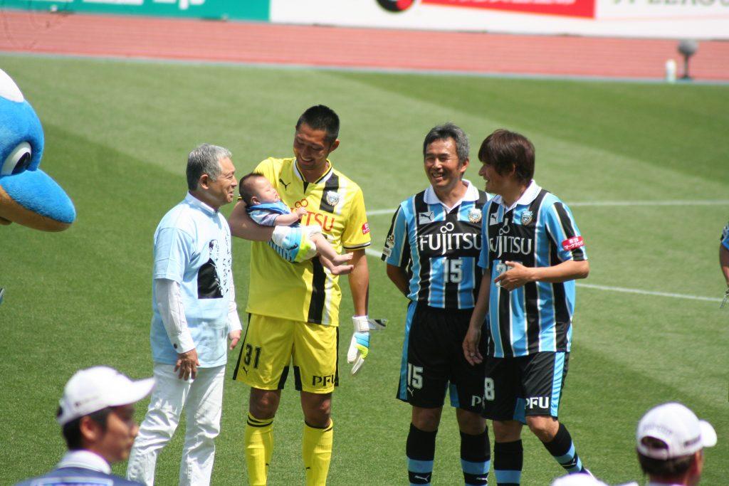 監督を務める松本育夫さんと笑顔の選手たち