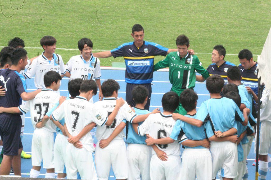 円陣を組むフロンターレの選手とコーチ陣