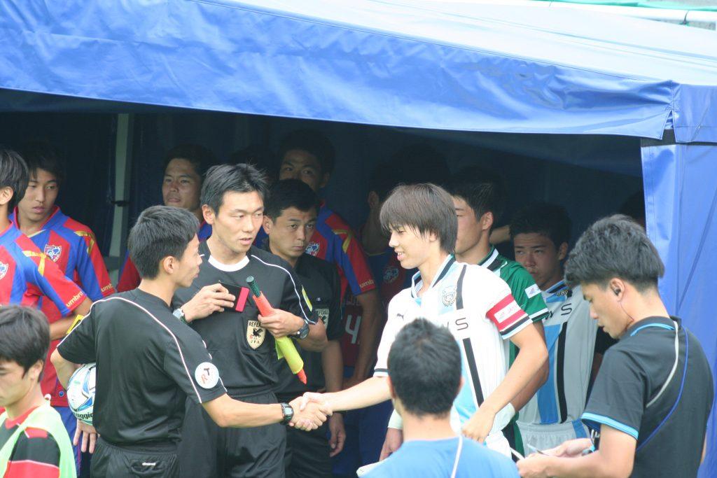 試合を前に審判と握手をかわす田中碧選手