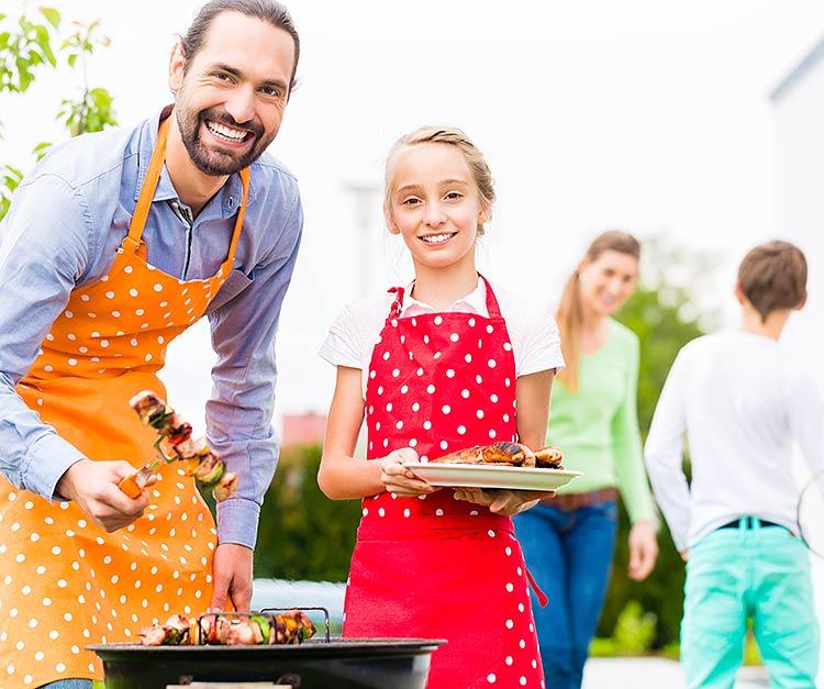 Isä ja tytär grillaavat pihatalkoissa.